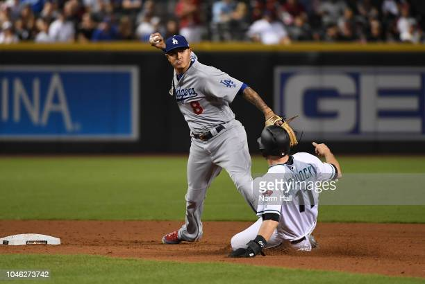 Manny Machado of the Los Angeles Dodgers turns a double play as AJ Pollock of the Arizona Diamondbacks slides into second base during the fifth...