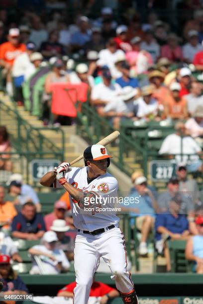 Manny Machado of the Orioles at bat in front with the Orioles fans in the background during the spring training game between the Boston Red Sox and...