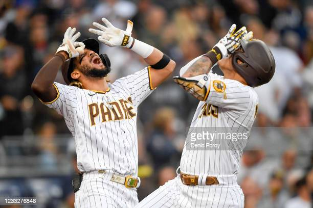 Manny Machado of the San Diego Padres celebrates with Fernando Tatis Jr. #23 after hitting a solo home run during the first inning of a baseball game...