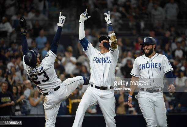 Manny Machado of the San Diego Padres center celebrates with Fernando Tatis Jr #23 left as Eric Hosmer looks on after Machado hit a solo home run...