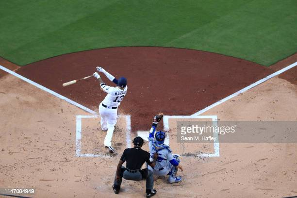 Manny Machado of the San Diego Padres connects for a solo homerun as Russell Martin of the Los Angeles Dodgers and umpire Alan Porter look on during...