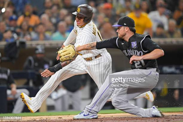 Manny Machado of the San Diego Padres is tagged out by Kyle Freeland of the Colorado Rockies as he tries to score on a wild pitch during the sixth...