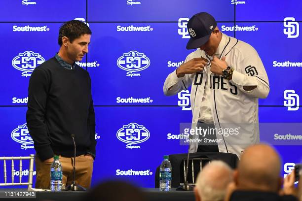 Manny Machado of the San Diego Padres puts on his new uniform alongside Executive V.P./General Manager A.J. Preller at Peoria Stadium on February 22,...