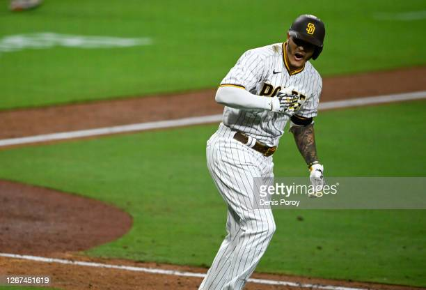 Manny Machado of the San Diego Padres reacts after hitting a walk-off grand slam during the 10th inning of a baseball game against the Texas Rangers...
