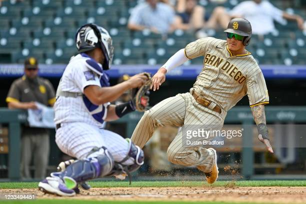 Manny Machado of the San Diego Padres slides into a tag by Elias Diaz of the Colorado Rockies for an out at home plate to end the fourth inning of a...