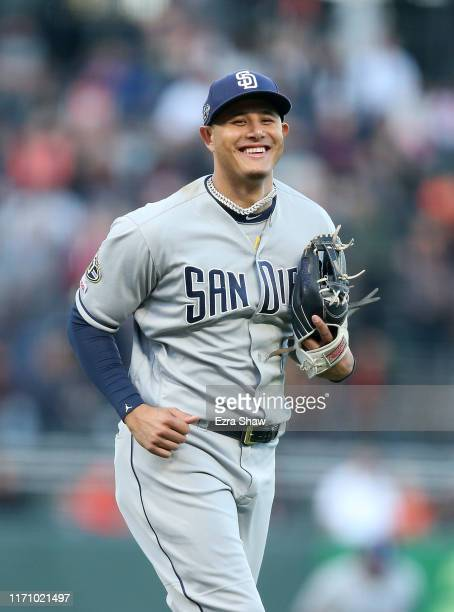 Manny Machado of the San Diego Padres smiles as he runs to the dugout after the first inning against the San Francisco Giants at Oracle Park on...