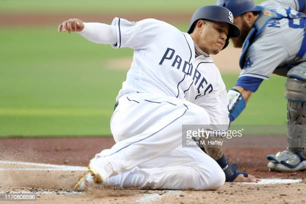 Manny Machado slides safely past Russell Martin of the Los Angeles Dodgers on a sacrifice fly by Hunter Renfroe of the San Diego Padres during the...