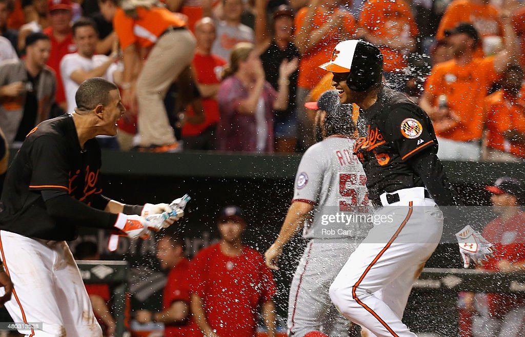 Manny Machado #13 sprays Jonathan Schoop #6 of the Baltimore Orioles with water after Schoop hit a walk off home run in the ninth inning to give the Orioles a 3-2 win over the Washington Nationals at Oriole Park at Camden Yards on July 10, 2015 in Baltimore, Maryland.