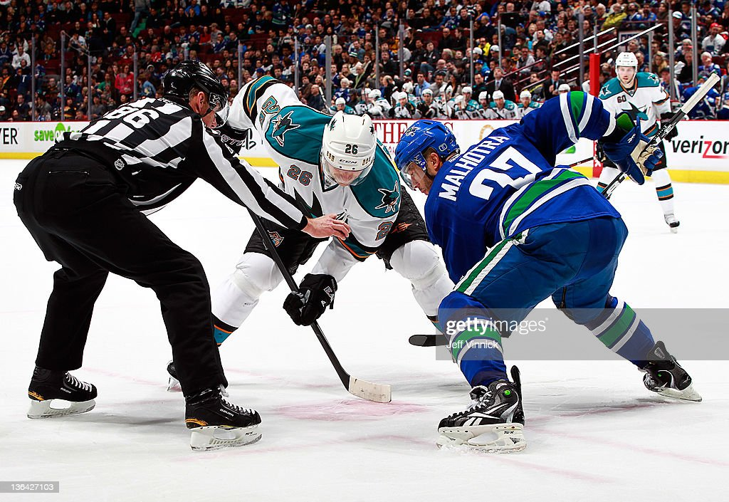 Manny Malhotra #27 of the Vancouver Canucks and Michal Handzus #26 of the San Jose Sharks square off for a face-off as linesman Brad Lazarowich prepares to drop the puck during their NHL game at Rogers Arena January 2, 2012 in Vancouver, British Columbia, Canada.