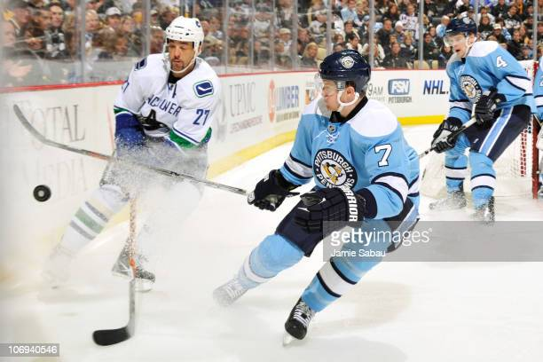 Manny Malhotra of the Vancouver Canucks and Paul Martin of the Pittsburgh Penguins race to a loose puck on November 17 2010 at Consol Energy Center...