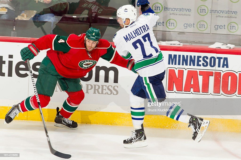 Manny Malhotra #27 of the Vancouver Canucks passes the puck with Clayton Stoner #4 of the Minnesota Wild defending during the game on February 7, 2013 at the Xcel Energy Center in Saint Paul, Minnesota.