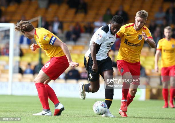 Manny Oyeleke of Port Vale moves forward witth the ball past Sam Foley and Ash Taylor of Northampton Town during the Sky Bet League Two match between...