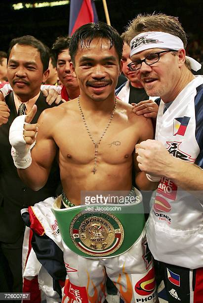 Manny Pacquiao of the Philippines celebrates his knockout victory against Erik Morales with his trainer Freddie Roach after their super featherweight...