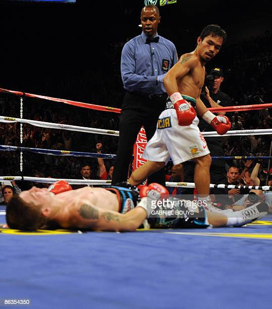 Manny Pacquiao of the Philippines looks at Ricky Hatton of England laying on the ring in the second round of their Junior Welterweight title fight at...