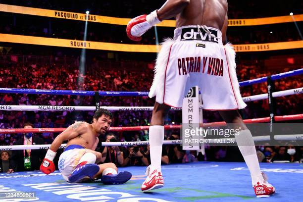 Manny Pacquiao of the Philippines looks at Yordenis Ugas of Cuba after a slip during the WBA Welterweight Championship boxing match at T-Mobile Arena...