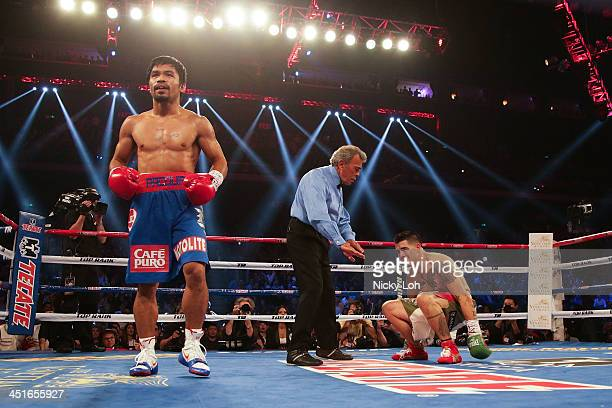 Manny Pacquiao of the Philippines walks away as Brandon Rios of the U.S. Falls during their 'Clash in Cotai' WBO International Welterweight title...