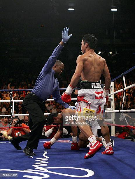 Manny Pacquiao of the Phillippines watches as referee Kenny Bayless calls the fight in the 10th round as Pacquiao knocked out Erik Morales of Mexico...