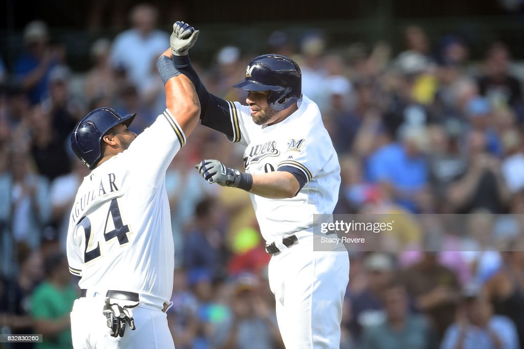 Manny Pina #9 of the Milwaukee Brewers is congratulated by Jesus Aguilar #24 following a two run home run during the eighth inning of a game against the Pittsburgh Pirates at Miller Park on August 16, 2017 in Milwaukee, Wisconsin.
