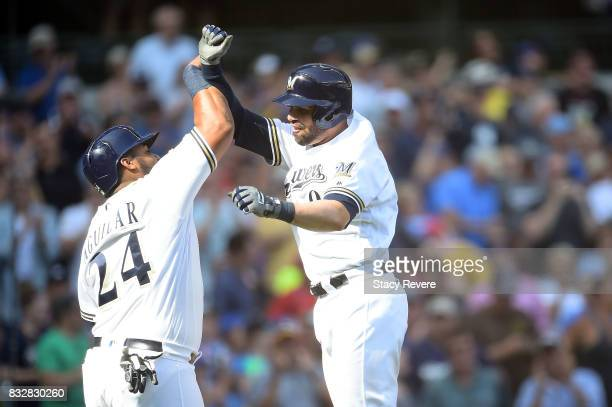 Manny Pina of the Milwaukee Brewers is congratulated by Jesus Aguilar following a two run home run during the eighth inning of a game against the...