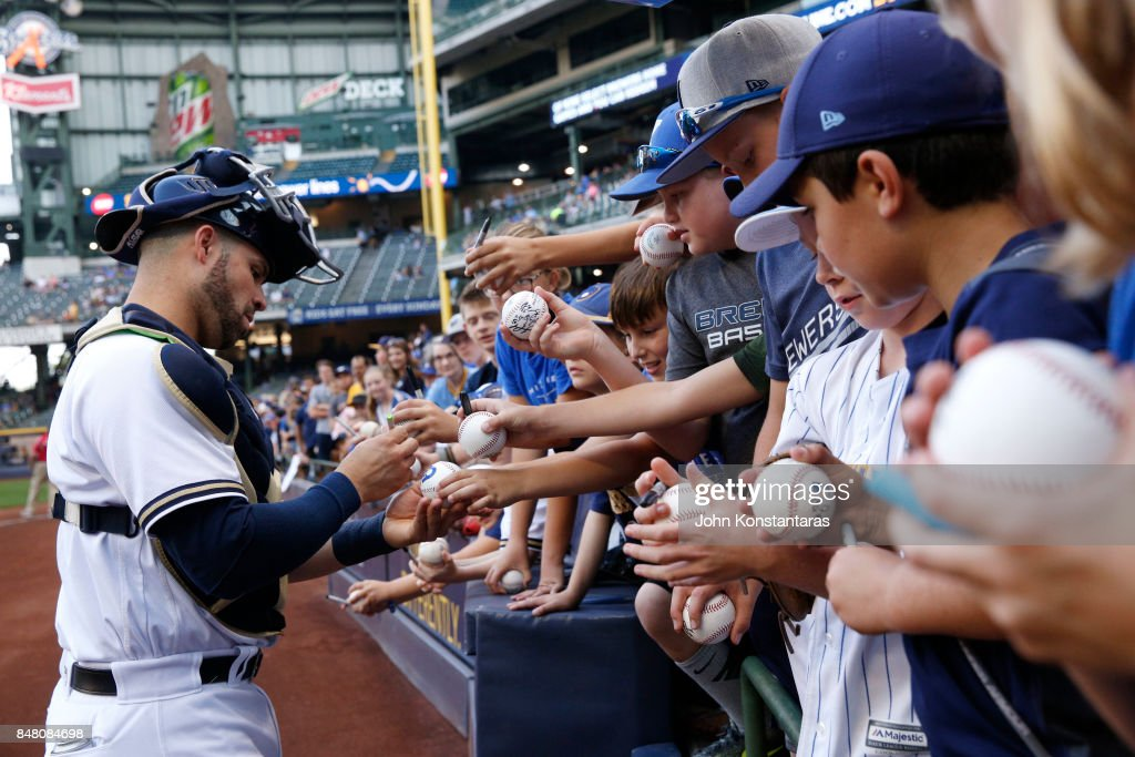 Manny Pina #9 of the Milwaukee Brewers signs autographs for fans before their game against the Miami Marlins at Miller Park on September 16, 2017 in Milwaukee, Wisconsin.