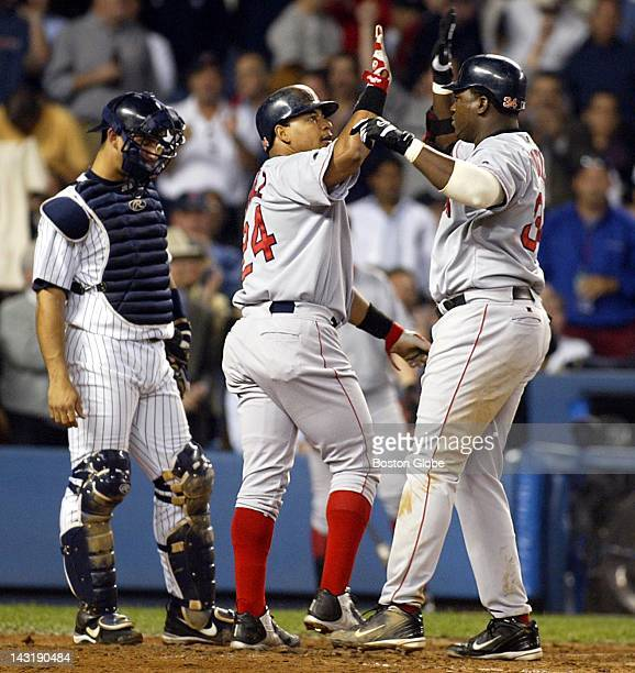 Manny Ramirez high fives David Ortiz after Ortiz' two run home run fourth inning Yankees catcher is Jorge Posada