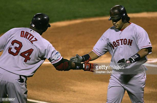 Manny Ramirez of the Boston Red Sox celebrates with teammate David Ortiz after hitting a solo home run against the St Louis Cardinals during the...