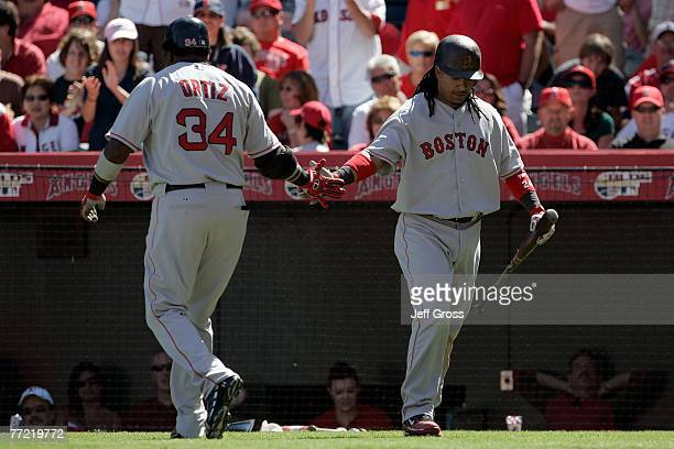 Manny Ramirez of the Boston Red Sox gives teammate David Ortiz a five after Ortiz hit a fourthinning home run off of Jered Weaver of the Los Angeles...