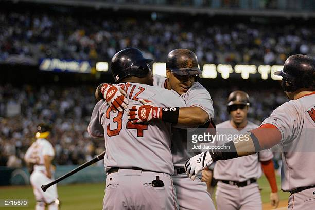 Manny Ramirez of the Boston Red Sox is congratulated by David Ortiz after hitting a threerun home run against the Oakland A's during the sixth inning...