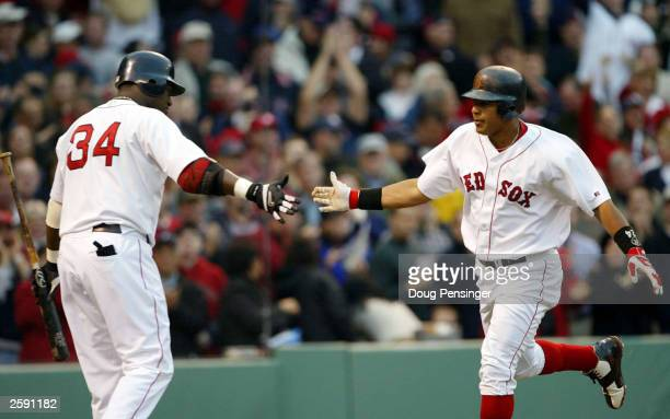 Manny Ramirez of the Boston Red Sox is congratulated by teammate David Ortiz after hitting a home run in the fourth inning of Game 5 of the 2003...