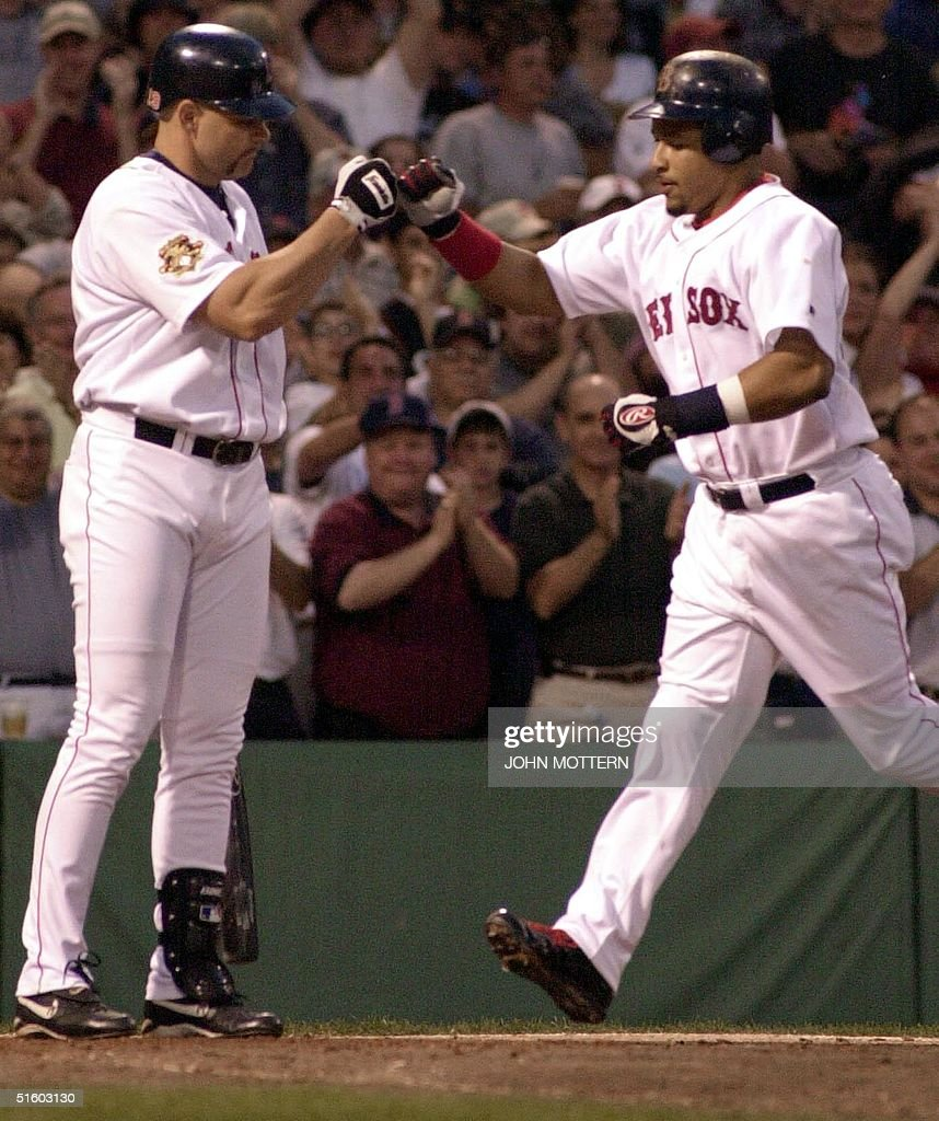 Manny Ramirez of the Boston Red Sox (R) is greeted by Dante Bichette (L) at home plate after hitting a fourth inning home run against the Philadelphia Phillies 08 June 2001 at Fenway Park in Boston, MA.