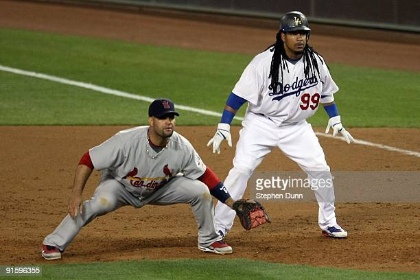 Manny Ramirez of the Los Angeles Dodgers is on base as he is held on by Albert Pujols of the St Louis Cardinals in Game One of the NLDS during the...