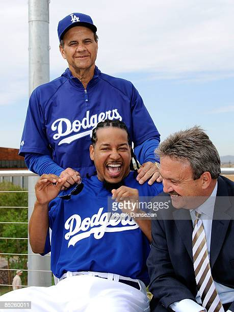 Manny Ramirez of the Los Angeles Dodgers smiles as manager Joe Torre and general manager Ned Colletti looks on during a news conference on March 5 at...