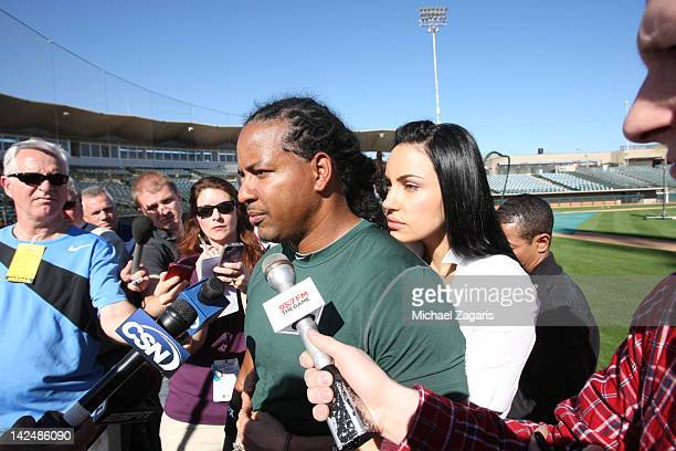 Manny Ramirez of the Oakland Athletics and his wife Juliana talk to the press following a workout during spring training at the Phoenix Municipal...