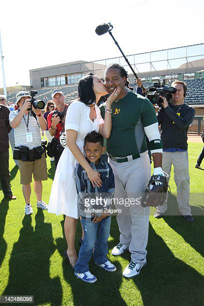 Manny Ramirez of the Oakland Athletics with his wife Juliana and son Lucas talk to the press following a workout during spring training at the...