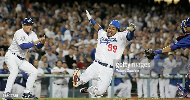 Manny Ramirez slides past the tage of Cubs catcher Geovany Soto as Dodgers third base coach Larry Bowa looks on in the first inning of game three of...
