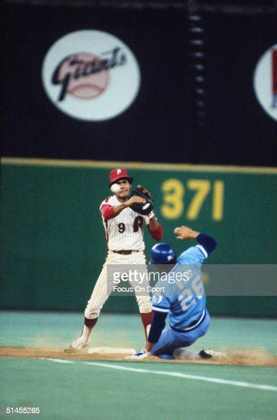 Manny Trillo of the Philadelphia Phillies guards 2nd base and throws to first while Amos Otis of Kansas City Royals slides in during the World Series...