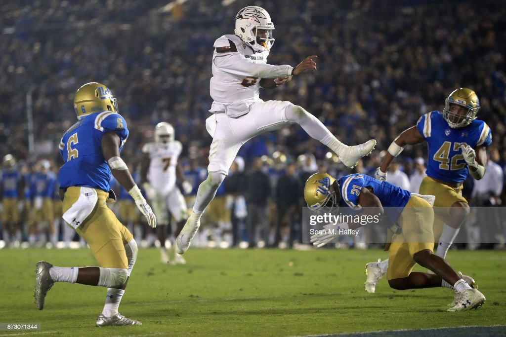 Manny Wilkins #5 of the Arizona State Sun Devils leaps past Adarius Pickett #6, Jamel Cook #21 and Kenny Young #42 of the UCLA Bruins for a touchdown during the first half of a game at the Rose Bowl on November 11, 2017 in Pasadena, California.