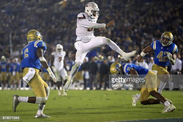 Manny Wilkins of the Arizona State Sun Devils leaps past Adarius Pickett, Jamel Cook and Kenny Young of the UCLA Bruins for a touchdown during the...