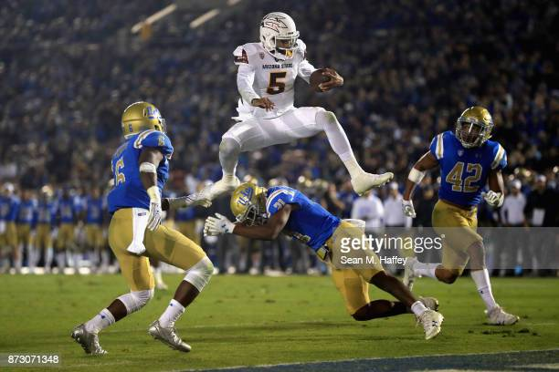 Manny Wilkins of the Arizona State Sun Devils leaps past Adarius Pickett Jamel Cook and Kenny Young of the UCLA Bruins for a touchdown during the...