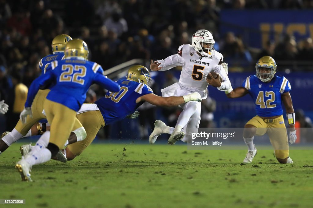 Manny Wilkins #5 of the Arizona State Sun Devils runs past Rick Wade #90, Nate Meadors #22 and Kenny Young #42 of the UCLA Bruins during the first half of a game at the Rose Bowl on November 11, 2017 in Pasadena, California.