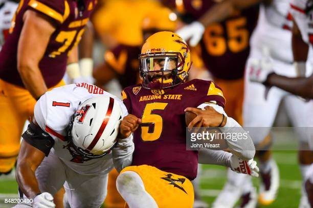 Manny Wilkins of the Arizona State Sun Devils slides to the ground and is hit by Jordyn Brooks of the Texas Tech Red Raiders during the game on...