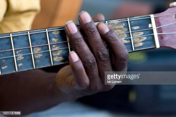 mano de jamaiquino tocando una guitarra rota - musical equipment stock pictures, royalty-free photos & images