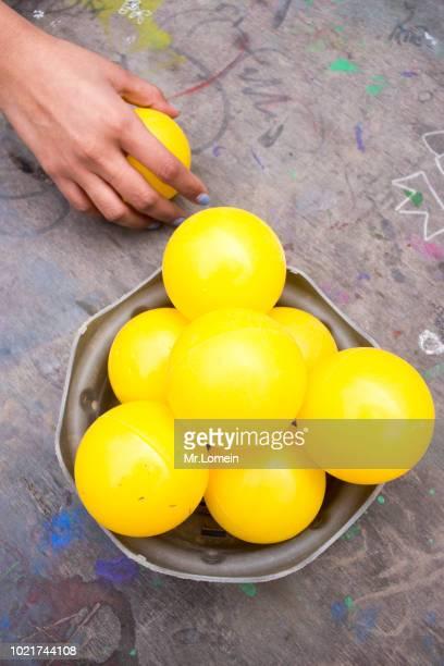 Mano de mujer con pelotas amarillas