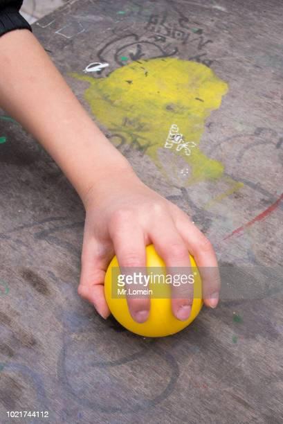 Mano de niño con pelotas amarillas
