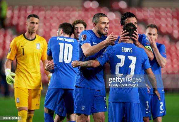 Manolis Siopis of Greece celebrates with team mates Giorgos Tzavellas and Kyriakos Papadopoulos following the FIFA World Cup 2022 Qatar qualifying...
