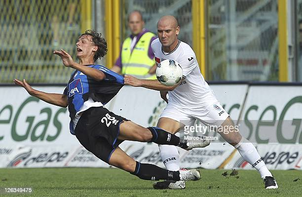 Manolo Gabbiadini of Atalanta BC competes for the ball with Andrea Lisuzzo of Novara Calcio during the Serie A match between Atalanta BC and Novara...