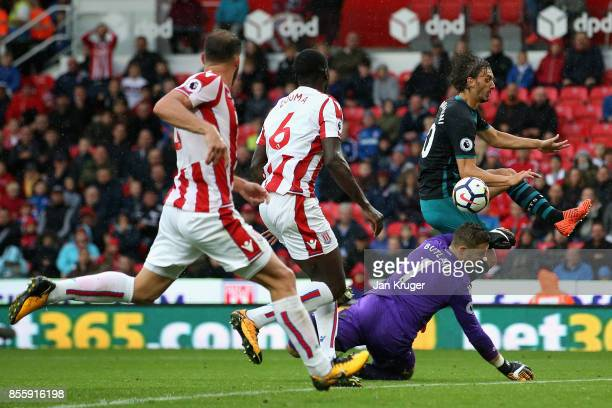 Manolo Gabbiadini of Southampton and Jack Butland of Stoke City collide during the Premier League match between Stoke City and Southampton at Bet365...