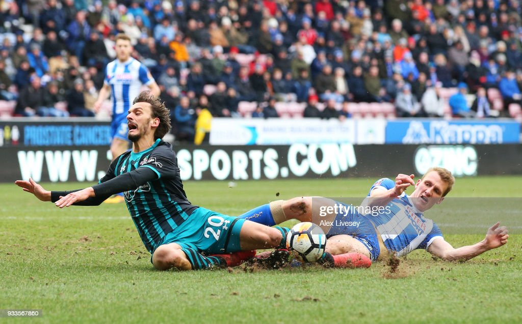 Manolo Gabbiadini of Southampton is fouled by Dan Burn of Wigan Athletic for a penalty during The Emirates FA Cup Quarter Final match between Wigan Athletic and Southampton at DW Stadium on March 18, 2018 in Wigan, England.