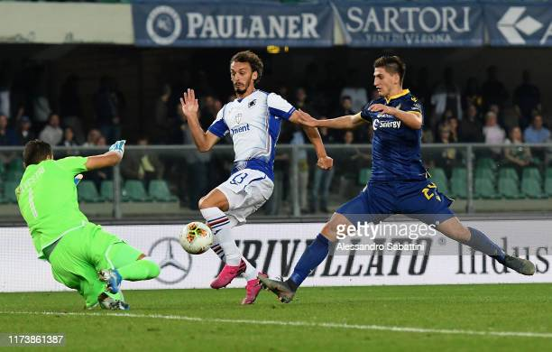 Manolo Gabbiadini of UC Sampdoria competes for the ball with Marco Silvestri of Hellas Veron during the Serie A match between Hellas Verona and UC...