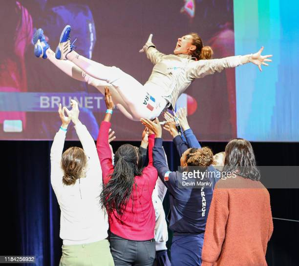 Manon Brunet of France is tossed into the air in celebratino of a win against Olga Nikitina of Russia during the gold medal round of competition at...